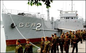 In this 2006 photo released by North Korea's Korea Central News Agency via Korea News Service, North Korean soldiers watch USS Pueblo, which was seized by North Korean navy off the Korean coast in Jan. 1968, near Taedonggang river in Pyongyang.