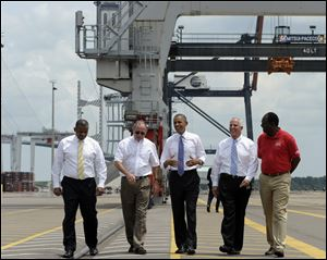 President Barack Obama, center, gets a tour of the Jacksonville, Fla. port today with, from left, Transportation Secretary Anthony Foxx; Dennis Kelly, TracPac Regional Vice President and General Manager; Ray Schleicher, CEO of the Jacksonville Port Authority, and Fred Wakefield, International Longshoreman's Association Representative,