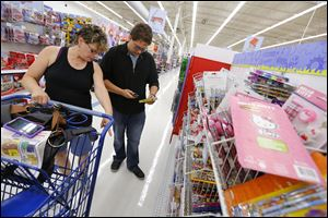 Jody Stribrny of Genoa and her son Joseph Stribrny, who will be a junior this year, shop for school supplies at Meijer in Rossford. A retail federation predicts the average family will spend $634.78 for school supplies, an 8 percent  drop from last year's $688.62.