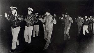In this photo released by the U.S. Navy, crew members of the USS Pueblo hold up their hands in captivity in North Korea in 1968.