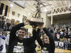 Perrysburg girls soccer team co-head coaches, Jorge Diaz, left, and Margaret Bernard hoist the MaxPreps Tour of Champions trophy during a ceremony at Perrysburg High School in January.
