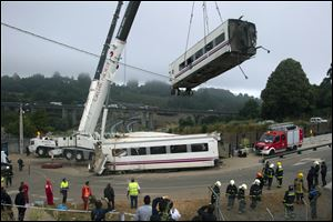 Derailed cars are removed as emergency personnel work at the site of a train accident in Santiago de Compostela, Spain.