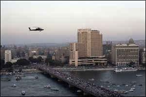 A military helicopter flies over protesters walking on a bridge leading to Tahrir Square today in Cairo.