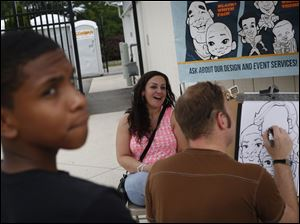 Terence Williams, 13, of Virginia Beach, left looks back at his niece Olivia Lau, 10, (not pictured) as artist Jamie Rockwell, right, completes a sketch of Williams' sister Angelina Ferguson, of West Toledo.