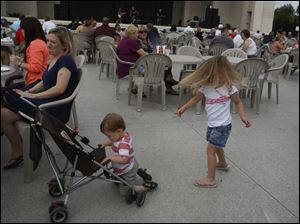 Norah Angel, 4, right, spins to the live music as her mother, Laura, of Sylvania, left, and brother Reid, 1, relax.