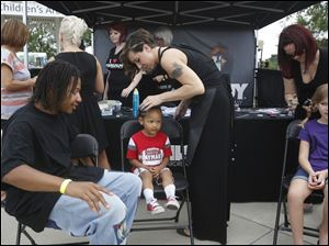 Troy Moody, of West Toledo, left, watches as his son Lareall, 3, center, has the tips of his braids dyed blue during this year's Pizza Palooza at Centennial Terrace in Sylvania KATIE RAUSCH