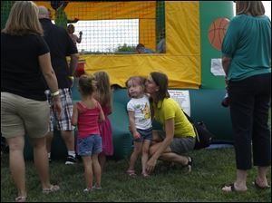 Gwendolyn Van Boren, of Slyvania, center right, gives her daughter Lore, 3, a kiss outside the bounce house.