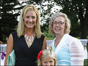 Martha Vetter, founder of Chicks for Charity, right, stands with Perrysburg resident Molly Kersten and her daughter Hannah, 7, during a fundraiser for Shared Lives Studio July 16, 2013 at the Toledo Botanical Garden.