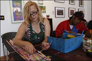 Shanna Richie, left, works on creating a weaving with pieces of canvas and Plexiglass glass as Marc Arnett works on a sky line of New York City during an art session at the Shared Lives Studio in downtown Toledo.