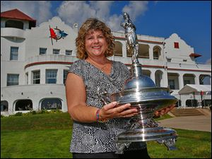Cheri Kaintz poses with the Emery D. Potter trophy at the Toledo Yacht Club. She saw the trophy in Colorado while visiting Rolly Hassett, who later gave it Kaintz so it could return to the club.