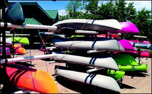 Racks of kayaks ready for sale fill the courtyard in front of Cabela's in Dundee.