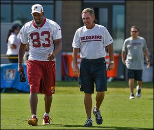 Redskins tight end Fred Davis walks with coach Mike Shanahan before practice on Friday. The Rogers grad is recovering from an Achilles injury.