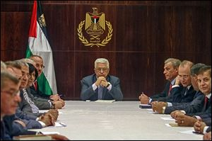 President Mahmoud Abbas, center, chairs a Palestinian cabinet session. He refused to engage in peace talks until Israel agreed to release 104 Palestinian prisoners.