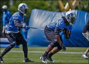 Detroit Lions running back Reggie Bush, left, holds back teammate Joique Bell during drills at training camp. Teammates admire Bush for the amount of extra work he puts in after practice.