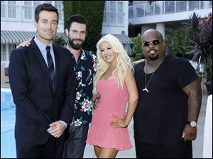 This image released by NBC shows, from left,  Carson Daly, Adam Levine, Christina Aguilera, and CeeLo Green at a cocktail reception.