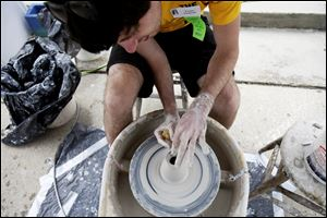 UT senior Taylor Pasquale throws clay on a potter's wheel during Art on the Mall on the University of Toledo campus.