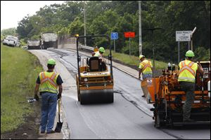Workers with the Ohio Department of Transportation pave the entrance ramp to I-475 westbound off Secor Road in West Toledo last month. The Ohio Department of Transportation's $1.3 million solution to long autumnal backups on I-475 at the exits closest to Westfield Franklin Park starts today.