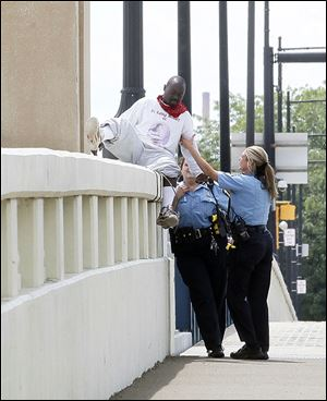 Toledo police officers help get George Armour III, 26, off the ledge of the Martin Luther King, Jr., Bridge after he threatened to jump.