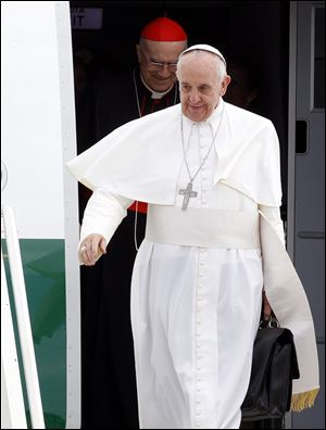 Pope Francis, holding his bag and followed by Vatican secretary of State Cardinal Tarcisio Bertone, disembarks from the plane after landing from Rio de Janeiro, Brazil, at Ciampino's military airport, on the outskirts of Rome, today. The pontiff returned after a week in Brazil.