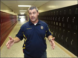 In this photo taken July 11, 2013, Cheyne Dougan, assistant principal at Clarksville High School, is interviewed at the school in Clarksville, Ark. Dougan is one of 20 Clarksville School District staff members are training to be armed security guards on campus. (AP Photo/Danny Johnston)