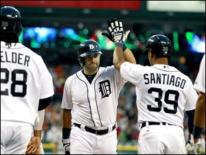 Detroit's Alex Avila, center, is congratulated after his grand slam by Prince Fielder, left, and Ramon Santiago in the sixth inning.