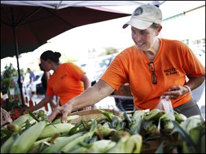 Cindy Bench of Bench Farms bags corn for a customer during the Farmer's Market in downtown Perrysburg. The market runs from 3 to 8 p.m. Thursdays.