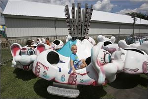 Caleb Singleton, 4, of Maumee sticks his tongue out while riding the Elephant Go Round at the Wood County Fair. Amusement rides for children, big and small, are a big fair attraction.