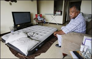 Jeffrey Fisher, president of the Alpha Towers residents' association, sits in his apartment Tuesday. Mr. Fisher sleeps on an air mattress because of an infestation of bed bugs. The Fair Housing Center has filed a complaint against Alpha Towers for nonworking elevators, bed bugs, and other issues.