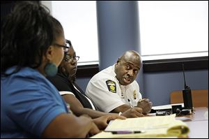 Police Chief Derrick Diggs speaks with One Village Council members Adita Miller, left, and Dawn Andrews at a meeting in North Toledo on Tuesday.