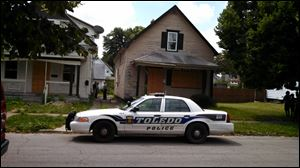 Authorities gather at 438 E. Streicher Street in North Toledo where a body was found in the basement.