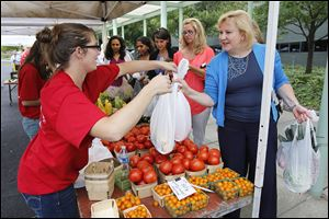 Jennifer Hummel of Andy Keil Greenhouse hands bags of fresh produce to Owens Corning employee Joyce Baranek, right, at the Toledo Farmers' Market, set up outside OC headquarters in downtown Toledo.
