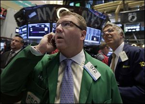 In this Monday, July 29, 2013, file photo, Trader Kevin Coulter, center, works on the floor of the New York Stock Exchange. Global stock markets drifted Wednesday July 31, 2013 as investors waited for the Federal Reserve's latest assessment of the U.S. economy.