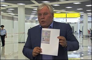 Russian lawyer Anatoly Kucherena shows a temporary document to allow Edward Snowden cross the border into Russia.