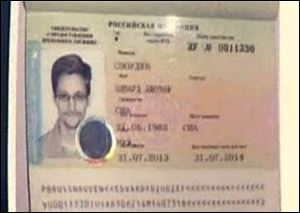 In this image taken form Russia24 TV channel, Russian lawyer Anatoly Kucherena shows Edward Snowden's  temporary document while speaking to the media after visiting the NSA leaker at Sheremetyevo airport outside Moscow, Russia.