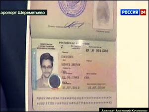 Russian lawyer Anatoly Kucherena shows Edward Snowden's a temporary document Russia while speaking to the media after visiting the National Security Agency leaker at Sheremetyevo airport outside Moscow Thursday.