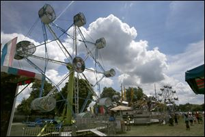 Rides spin as fair goers walk the grounds in the sunshine during this year's Wood County Fair Tuesday in Bowling Green.