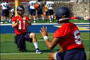 Freshman quarterback Logan Woodside (11) warms up with freshman quarterback Michael Julian (5) during practice.
