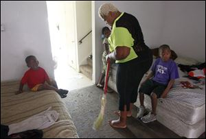 Carlee Carter sweeps the floor to rid it of bugs that infest her home at the Greenbelt Place apartment complex along Cherry Street. Her children, from left, Adron, 3, Shydoria, 7, and Joseph, 8, all sleep in that room to avoid roaches that scurry across the carpet in the upstairs bedrooms.
