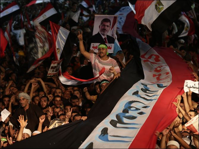 Supporters of Egypt's ousted President Mohammed Morsi  hold a large Egyptian national flag as chant slogans against Egyptian Defense Minister Gen. Abdel-Fattah el-Sissi outside Rabaah al-Adawiya mosque.