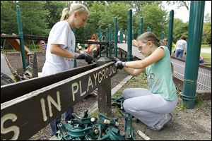 Samantha Hirsch, 11, and her sister Sydney Hirsch, 8, dismantle a playground sign at Pearson Metropark in Oregon. The 11,000-square-foot area will be the site of a larger play­s­cape in the fall.