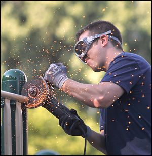 BP-Husky worker Dave Simons saws off a steel railing from the playground at Pearson Metropark in Oregon.