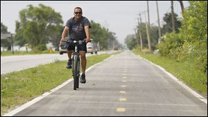 Oregon resident Alfonso Ummel rides along the recently completed Oregon Parks Bike Trail, which connects Pearson Metropark and Maumee Bay State Park.