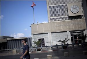 A man walks past the U.S Embassy in Tel Aviv, Israel, Sunday.