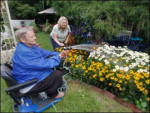 John Sharkey waters his flowers in West Toledo home garden in Toledo. Picking weeds is his daughter Susan Sharkey.