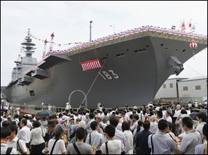 Japan's new warship Izumo, which has a flight deck that is nearly 820 feet long, is unveiled in Yokohama, south of Tokyo, today.