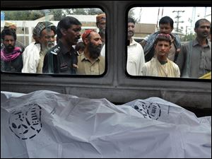 People look at the lifeless bodies of victims shot by gunmen at a local hospital in Quetta, Pakistan, Tuesday, Aug. 6, 2013. Dozens of gunmen disguised in police uniforms shot to death more than a dozen they pulled off of a convoy of buses in southwest Pakistan and dumped their bodies in a nearby ravine, officials said Tuesday. (AP Photo/Arshad Butt)