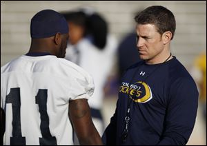 Jason Candle, passing game coordinator, speaks with a Rockets player at a 2012 practice.