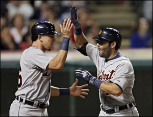 Detroit Tigers' Alex Avila, right, celebrates with Hernan Perez after Avila's three-run home run off Cleveland Indians relief pitcher Chris Perez in the ninth inning.