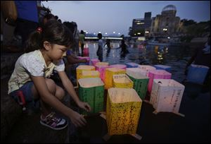 A girl releases a paper lantern for the repose of the soul of her great grandmother who died in the atomic bombing in the Motoyasu River with the backdrop of the Atomic Bomb Dome in Hiroshima, western Japan, Tuesday.