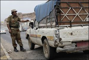 A Yemeni soldier stops a car at a checkpoint in a street leading to the U.S. embassy in Sanaa, Yemen, Sunday.